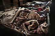 Newly-arrived victims of sexual violence share the beds inside Kichanga Transit Center, supervised by Mama Jeanne, the responsible counselor for Hope in Action/CRN. The age of rape victims range from two years old to over sixty years old. These women here will wait until the beds in Goma's hospital will be available and get treated. The transit center receives between 10-15 victims of sexual violence in various villages in and around Kichanga, and only has 15 beds. They usually share a bed like these women here, or sleep on the floor in the saloon.