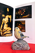 fake bird perched on a rock placed in front of art book on historical paintings from the Prado museum