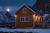 Yellow Cabin at Sakrisøy with rising winter moon in background, Lofoten Islands, Norway