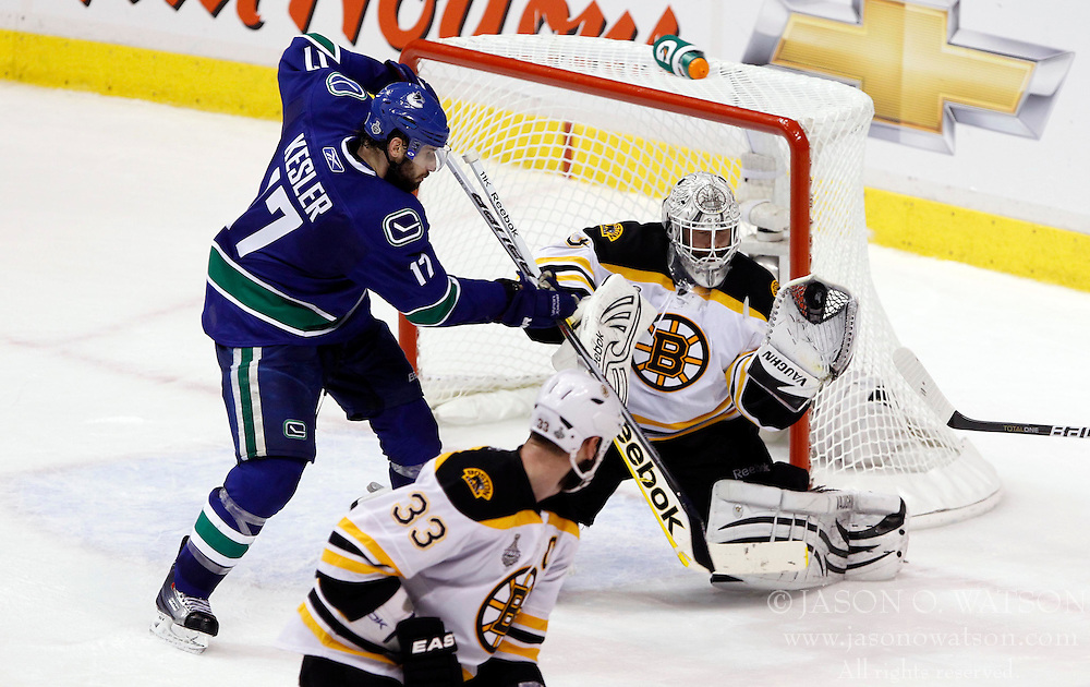 June 1, 2011; Vancouver, BC, CANADA; Boston Bruins goalie Tim Thomas (right) makes a glove save as Vancouver Canucks center Ryan Kesler (17) looks for the rebound during the second period in game one of the 2011 Stanley Cup Finals at Rogers Arena. Mandatory Credit: Jason O. Watson / US PRESSWIRE