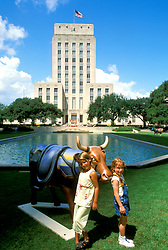 Stock photo of two young girls standing in front of City Hall alongside a Houston Cow Parade cow.