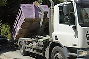 Truck unloading an empty container for building material waste