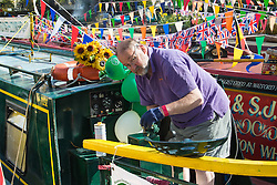 Little Venice, London, May 1 2016. Bright sunshine greets narrow boaters at the Inland Waterways Association's annual Canalway Cavalcade, a get-together of narrow boaters from all over the UK, on the May Day bank holiday. PICTURED: A narrow boater polishes the brasswork on his vessel. ©Paul Davey<br /> FOR LICENCING CONTACT: Paul Davey +44 (0) 7966 016 296 paul@pauldaveycreative.co.uk