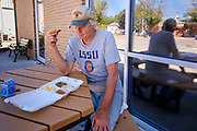 """02 SEPTEMBER 2020 - MITCHELLVILLE, IOWA: JERRY BUTLER eats his lunch in front of the library in Mitchellville. He gets a hot lunch at the library nearly every day. There is no grocery store in Mitchellville, a small community in eastern Polk County. It doesn't qualify as a """"food desert"""" under USDA guidelines because there are grocery stores within 10 miles in neighboring communities, but based on state data, Mitchellville is the poorest community in Polk County (which includes the Des Moines metropolitan area). The Mitchellville zip code has the lowest per capita income in Polk County. Many people don't own cars and can't get to neighboring communities to buy groceries. The library in Mitchellville has made arrangements with a neighboring community. Every day someone from the Mitchellville library picks up hot meals from a nearby town and distributes them in the library parking lot.      PHOTO BY JACK KURTZ"""