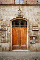 Photo of a dramatic entryway off of the streets of San Quirico d'Orcia, Italy.