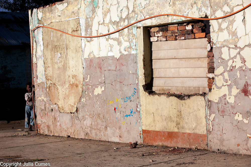 """A young boy peeks around the corner of one of """"Skomplaas"""" hostel's crumbling buildings on the outskirts of Johannesburg, South Africa."""