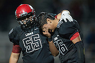 Westminster's Gabriel Moreno consoles Andrew Acosta after the Lions' 41-38 overtime loss to Segerstrom High Thursday night at Boswell Field in Westminster.