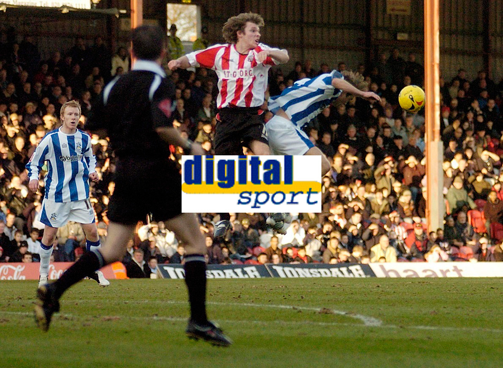 Photo: Leigh Quinnell.<br /> Brentford v Huddersfield Town. Coca Cola League 1. 21/01/2006. Brentfords Jay Tabb clashes with Huddersfields Chris Brandon in the air. After this fowl Brentfords Ricky Newman was sent off.