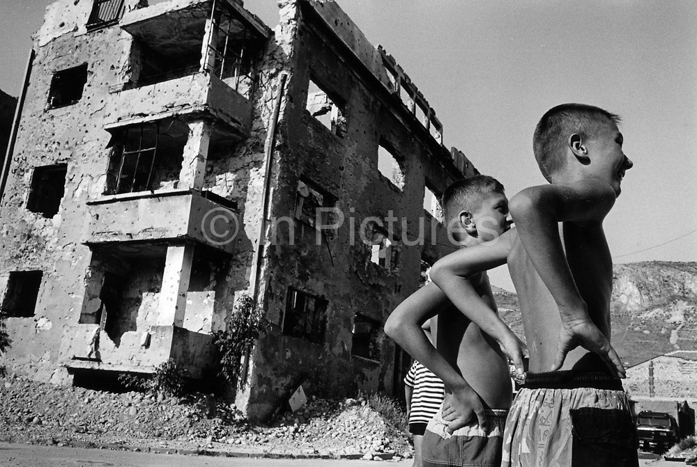 "Boys playing basketball in the ruins on the front line between Muslim East Mostar and Croat West Mostar. It was destroyed by systemic bombardment from Croat guns during the Croat Muslim War, when the Croats endeavored to "" cleanse"" the town of non Croats. Mostar, Bosnia and Herzegovina."