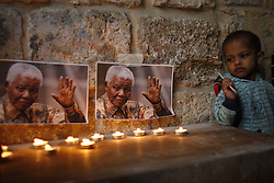 JERUSALEM, Dec. 7, 2013  Candles are placed in front of printed photographs of South African former president Nelson Mandela during a vigil by Palestinians and members of the African community in the Old City of Jerusalem, on Dec. 7, 2013. Best known for his long struggle against apartheid, Mandela passed away Thursday night at the age of 95 in Johannesburg following a prolonged battle with a lung infection. (Xinhua/Muammar Awad) (Credit Image: © Muammar Awad/Xinhua/ZUMAPRESS.com)