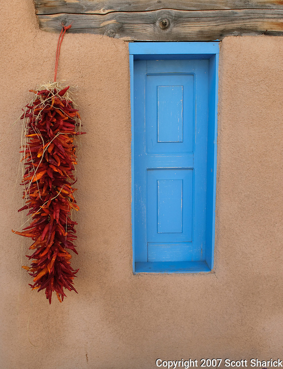 A closed blue window and a red hot chile ristra in New Mexico