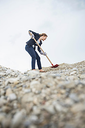 Businesswoman digging shovel into stone covered hill, Munich, Bavaria, Germany, Europe