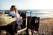 Woman taking photos from a landrover parked on the slipway at St Ouen's Bay, Jersey, CI of the sun, sea and surf.