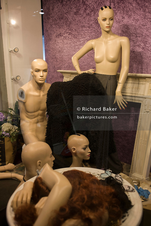 Shop mannequins await dressing and styling in central London window.