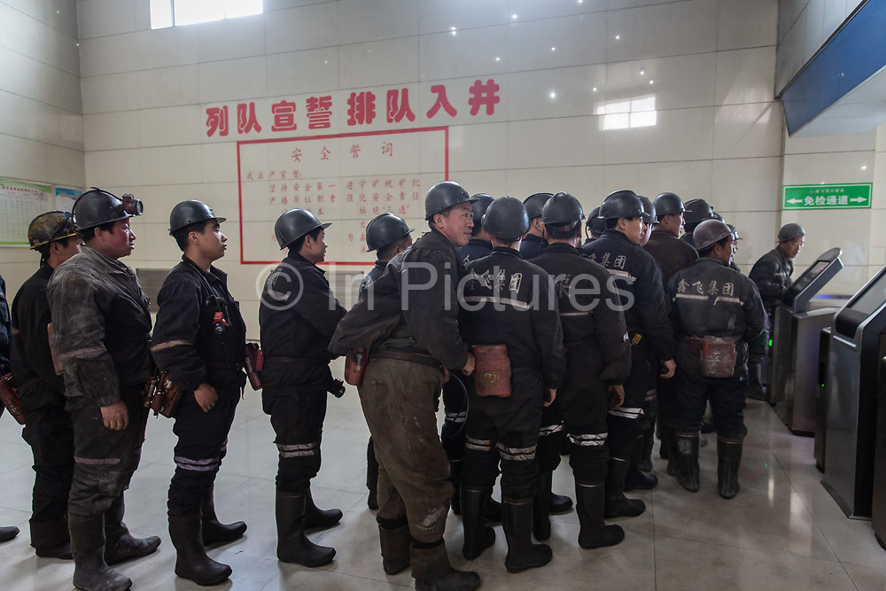 Miners line up to enter the shaft and begin their shift at a coal mine and processing facility in Liulin, Shanxi province, China, on Thursday, May 19, 2016. Shanxi is facing a challenge shared by a sweeping region across Chinas industrial north: how to shut down cash-burning mines that employ millions of people whose prospects are uncertain in the new economy promised by President Xi Jinping.