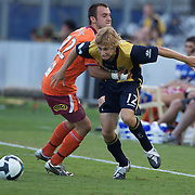 Matthew Lewis (right) is tackled by Ivan Franjic during the Central Coast Mariners V Brisbane Roar A-League match at Bluetongue Stadium, Gosford, Australia, 19 December 2009. Photo Tim Clayton