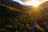 Aerial view of Ogden Canyon as the setting sun warms the colorful Fall colors along the river and road.