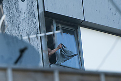June 14, 2017 - London, London, UK - London, UK. A distressed, trapped man waves an item of clothing from his window, at the scene of a huge fire at Grenfell tower block in White City, London. The blaze engulfed the 27-storey building with 200 firefighters attending the scene. There were reports of people trapped in the building. (Credit Image: © Guilhem Baker/London News Pictures via ZUMA Wire)