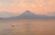 Early morning view across Lake Atitlan from Panajachel. A canoeist paddles in front of  Volcan San Pedro 3020m.. Panajachel, Republic of Guatemala. 04Mar14.