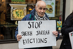 Pro-Palestinian activist Eric Levy, 92, holds a sign calling for an end to evictions in Sheikh Jarrah at a protest outside the UK headquarters of Elbit Systems, an Israel-based company developing technologies used for military applications including drones, precision guidance, surveillance and intruder-detection systems, on 11th May 2021 in London, United Kingdom. Activists from Palestine Action were protesting against the company's presence in the UK and in solidarity with the Palestinian people following attempts at forced evictions of Palestinian families in the Sheikh Jarrah neighbourhood of East Jerusalem, the deployment of Israeli forces against worshippers at the Al-Aqsa mosque during Ramadan and air strikes on Gaza which have killed several children.