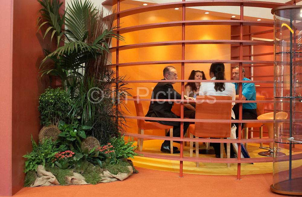 Four business partners are in the middle of a meeting at the Paris Air Show, Le Bourget France. Seated within a private area that looks like a cage, they engage in conversation on this stylish stand that also features a lush oasis of green vegetation. The Paris Air Show is a commercial air show, organised by the French aerospace industry whose purpose is to demonstrate military and civilian aircraft to potential customers.