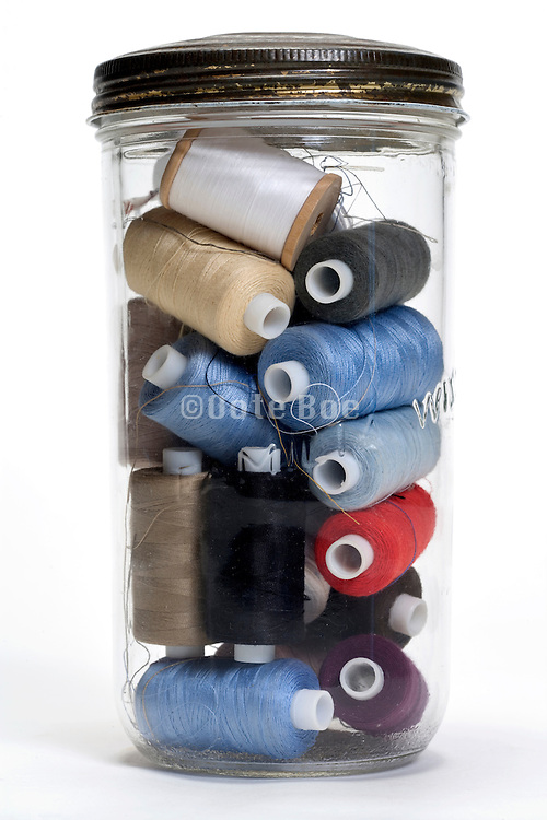 round spools with thread in glass jar