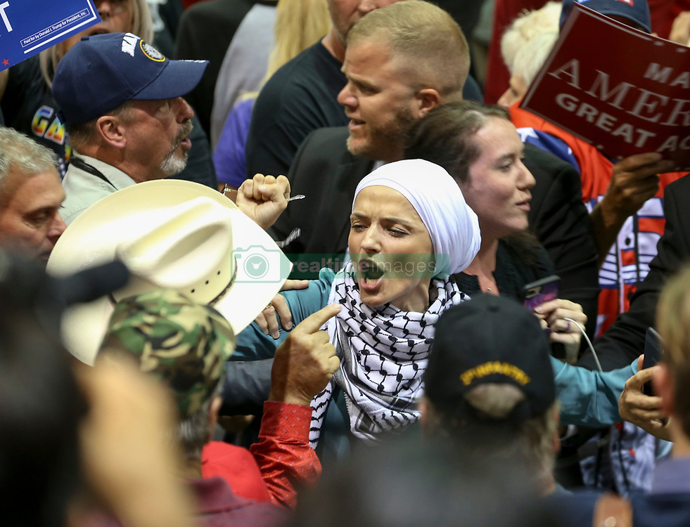 July 31, 2018 - Tampa, Florida, U.S. - AIDA MACKIC, a 35-year-old Tampa mother of four, is removed from President Donald Trump's rally at the Florida State Fairgrounds on Tuesday as  supporters of the President argue with her. Mackic, a Muslim woman who wears a traditional head scarf, was one of six women who shouted, 'Immigrant rights are human rights.'  'I didn't think I'd experience that much anger from humans who don't even know me,' Mackic, a 35-year-old married mother of four who immigrated to the United States as a child from war-torn Bosnia, said during an interview Wednesday. (Credit Image: © Chris Urso/Tampa Bay Times via ZUMA Wire)