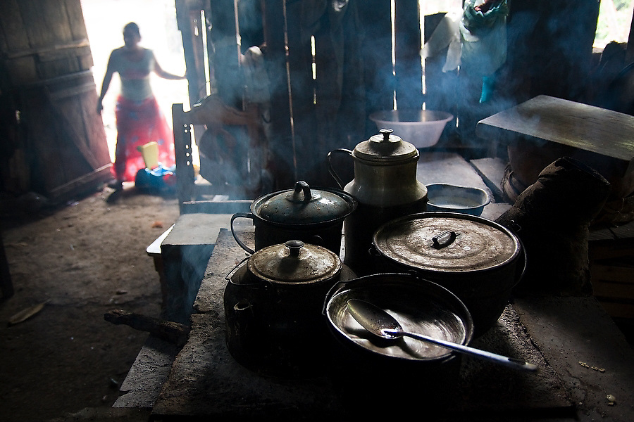 A woman enters a home in the Lacandon Maya community of Naha, Chiapas, Mexico on July 4, 2008 while smoke rises from a wood burning stove covered with metal pots.