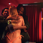 Two ex-prostitutes, both former heavy drug users, hug a sex worker in Amsterdam's Red Light district. ..The woman on the left is from Surinam, a former Dutch colony. She used to be a heroine addict. The woman on the right is from Ivory Coast, where she worked as a street prostitute before being sold to Amsterdam 20 years ago. Through religious faith, they both kicked off their addiction and spend much of their time healing others...The woman in the middle, a 17-year-old Dutch, said she prostitutes herself to gain the love of her boyfriend...The healers belong to Victory Outreach, a controversial church started in Los Angeles in 1967, is spreading to Europe via the Netherlands. It builds its membership among junkies, prostitutes and criminals. ..Photo taken in the Netherlands in 2002. The picture is part of a photo and text documentary by Justin Jin. For more information, email justin@justinjin.com