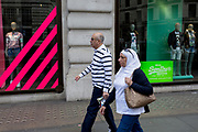 A shopper wearing stripes walks past the window of fashion brand Superdry, on 18th April 2017, in London, England.
