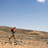 26 March 2007: #320 Nicolas Margarot of France runs across a very rocky plain during the second stage (21.7 miles) of the 22nd Marathon des Sables between Khermou and jebel El Otfal. The Marathon des Sables is a 6 days and 151 miles endurance race with food self sufficiency across the Sahara Desert in Morocco. Each participant must carry his, or her, own backpack containing food, sleeping gear and other material.
