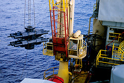 Stock photo of a crane lifting metal components from the ocean