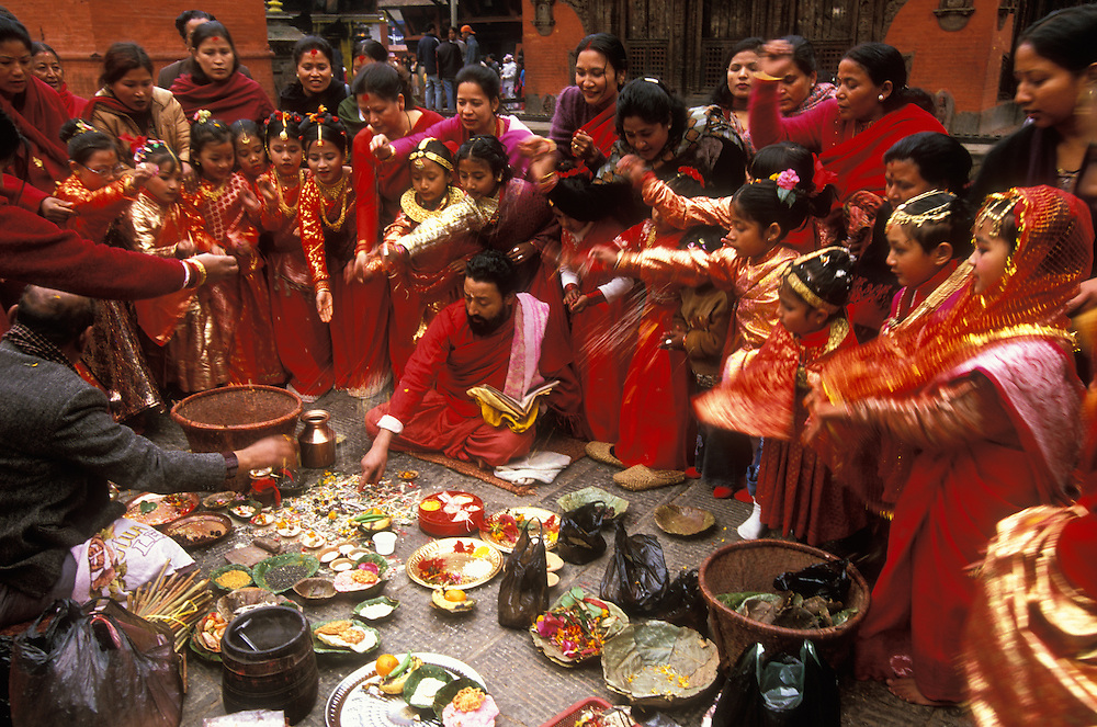Girls and their mothers scatter grains of rice as an offering to the gods while a priest conducts the rituals for the girls' Ihi ceremony, a mock marriage to the Hindu god Vishnu, in Patan in the Kathmandu Valley, Nepal. Among the Newars, who are the original inhabitants of the Kathmandu Valley, every girl goes through this ceremony sometime between the age of five and ten. The Ihi makes the girl a full member of her father's family and caste and is also said to make sure that she will never become a widow, even if later on her future human husband would die, since she will forever be married to the god Vishnu. The Ihi is therefore for the Newar women a protection against the stigmatization of widows otherwise common in Hindu culture.