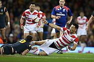Akihito Yamada of Japan gets his pass away despite getting his shorts pulled down by Lloyd Williams of Wales.  Under Armour 2016 series international rugby, Wales v Japan at the Principality Stadium in Cardiff , South Wales on Saturday 19th November 2016. pic by Andrew Orchard, Andrew Orchard sports photography