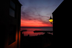 © Licensed to London News Pictures. <br /> 05/05/2016. <br /> Staithes, UK.  <br /> <br /> A street lamp shines from a wall as the dark red glow of first light reaches over the harbour in the small North Yorkshire fishing village of Staithes.<br />   <br /> Photo credit: Ian Forsyth/LNP