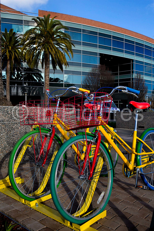 Multi coloured, branded  Google bicycles outside the Google global HQ in Mountain view, California for employees to travel round the google campus and offices