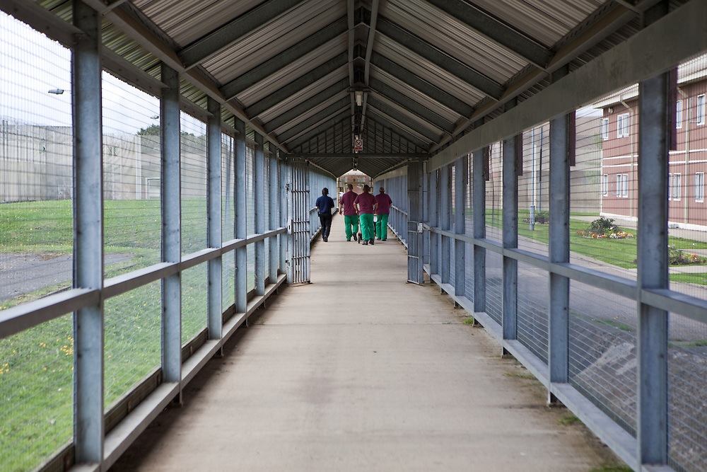 Prisoners walk through a secure walkway linking some of the prison buildings. HMP The Mount, Bovingdon, Hertfordshire