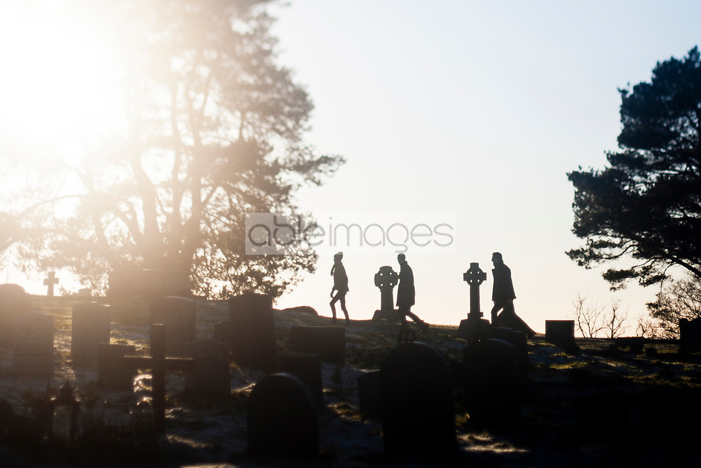 Silhouette of People Walking through Graveyard