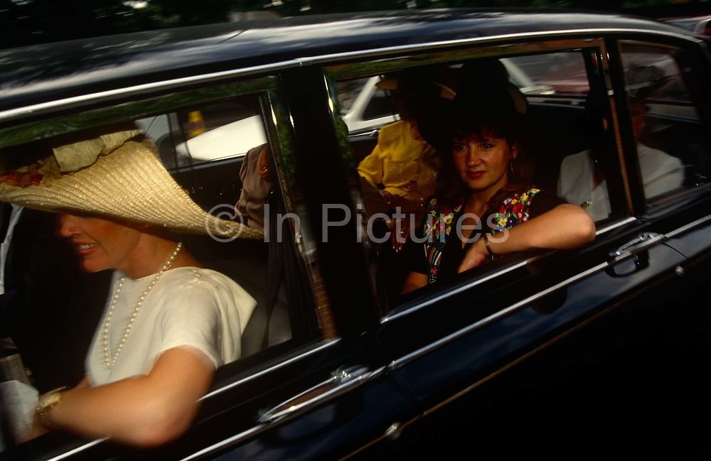 A car-load of women travel towards Ascot in a rented limousine on Ladies Day at Royal Ascot racing week. With wide-brimmed hats taking up space in the low-roofed executive car, the ladies look excited at a day of horse racing and bubbly. Royal Ascot is held every June and is one of the main dates on the sporting calendar and English social season. Over 300,000 people make the annual visit to Berkshire during Royal Ascot week, making this Europe's best-attended race meeting. There are sixteen group races on offer, with at least one Group One event on each of the five days. The Gold Cup is on Ladies' Day on the Thursday. There is over £3 million of prize money on offer.