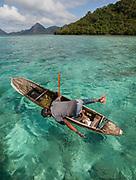 Looking underwater for octopus. Fisherman named Tarumpit fishing with duggout canoe off Boheydulang island.
