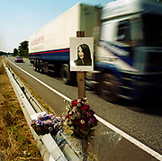 "A memorial has been placed where 'Amy' died on the A27 near Binstead, Sussex, England. If we drove past this place where someone's life ended, the victim would just be a statistic but flowers are left to die too with touching poems written by family and loved-ones: ""To Amy (aged 14)/In my heart there is a picture worth more than silver and gold/it is a picture of my auntie Amy/whose memory will never grow old/Death comes so very quick/you never know when you're going to be picked."" From a project about makeshift shrines: ""Britons have long installed memorials in the landscape: Statues and monuments to war heroes, Princesses and the socially privileged. But nowadays we lay wreaths to the ordinary who die suddenly - killed as pedestrians, as drivers or by alcohol, all celebrated on our roadsides and in cities with simple, haunting roadside remembrances"