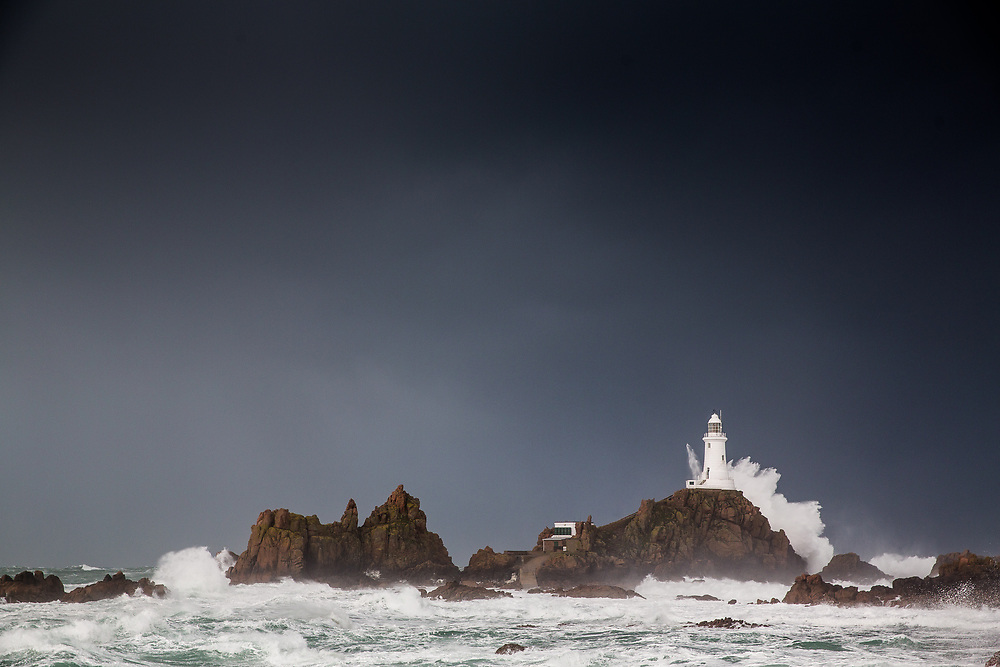 Dark stormy sky and waves crashing behind Corbiere Lighthouse in jersey, Channel Islands