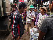 16 JUNE 2014 - POIPET, CAMBODIA: Cambodian vendors walk between the army trucks taking Cambodian migrants back to their home villages in Poipet, Cambodia. More than 150,000 Cambodian migrant workers and their families have left Thailand since June 12. The exodus started when rumors circulated in the Cambodian migrant community that the Thai junta was going to crack down on undocumented workers. About 40,000 Cambodians were expected to return to Cambodia today. The mass exodus has stressed resources on both sides of the Thai/Cambodian border. The Cambodian town of Poipet has been over run with returning migrants. On the Thai side, in Aranyaprathet, the bus and train station has been flooded with Cambodians taking all of their possessions back to Cambodia.  PHOTO BY JACK KURTZ