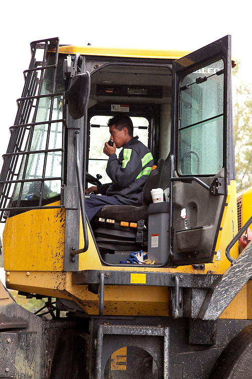 Man drives and operates front end loader at municipal solid waste transfer station
