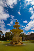 The Hochgurtel fountain in front of Melbourne's Royal Exhibition Building was designed in 1880 by Joseph Hochgurtel, an immigrant from Cologne, and his colleague August Saupe. The fountain represents innocence and potential of youth, along with  symbols of industry, science, commerce and art; a steam engine, telescope, surveying implements, a sailing ship, a globe of the world and musical instruments.