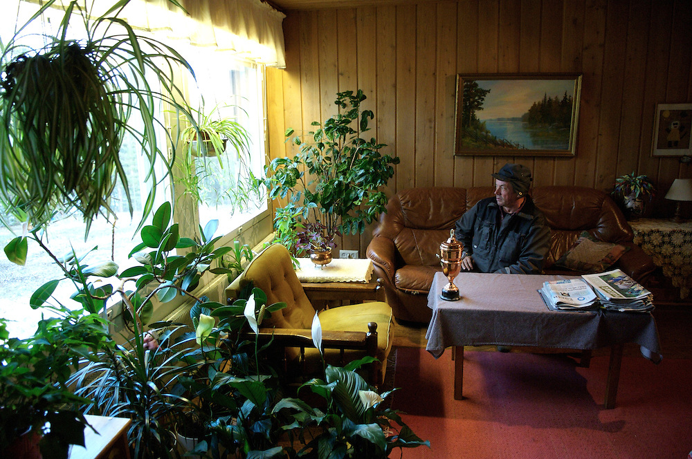 Hirvas Salmi, FINLAND.  With a trophy he won in 1977 for the champion lasso thrower in all of Scandinavia, Veggai, 58, looks out onto his lake.  In addition to working as a Sami Herdsman he also has a penchant for gardening.