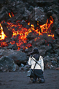 A girl observes the flowing lava from the erupting volcano on Fimmvörðuháls, south Iceland 2010
