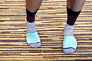 male person on striped carpet wearing colorful striped socks