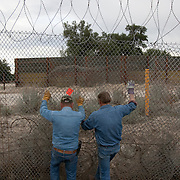 Bob Maupin has lived on the U.S./Mexico border for over 60 years in eastern San Diego County. His fence abuts Mexico and is often used by migrant and drug smugglers to illegally enter the United States. Much of Bob's day, including Inauguration Day on January 20, 2009, is devoted to checking his fence and property for signs of illegal entry. Here, neighbor Dick Buck, a Minuteman Civil Defense Corps volunteer, helps Bob repair the fence cut by smugglers. Please contact Todd Bigelow directly with your licensing requests.