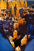 Bryce Canyon's Paria Point in winter. Bryce Canyon National Park, a sprawling reserve in southern Utah, is known for crimson-colored hoodoos, which are spire-shaped rock formations. The park's main road leads past the expansive Bryce Amphitheater, a hoodoo-filled depression lying below the Rim Trail hiking path. It has overlooks at Sunrise Point, Sunset Point, Inspiration Point and Bryce Point. Prime viewing times are around sunup and sundown.